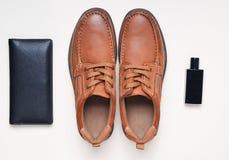 Man& x27; s神色 有棕色皮革的,钱包,一个瓶鞋子淡色表面上的香水 库存照片