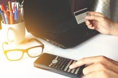 Man& x27; s übergibt das Halten einer Kreditkarte über Laptop und die Anwendung von calculat Stockbilder