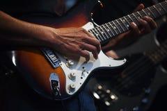 Man& x27; s вручает играть на электрической гитаре в диапазоне на этапе, en Стоковые Изображения RF