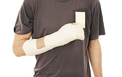 Man's arm in cast holding a blank card Royalty Free Stock Photography