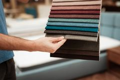 Man`s arm chooses color on color palette. Selecting color of mattress on color palette guide royalty free stock images