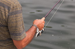 Mans arm with fishing rod beside lake Stock Photos