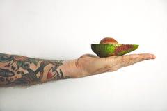 Man`s arm with half of avocado stock photo