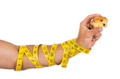 Man's arm wrapped in measuring tape holding muffin Royalty Free Stock Photography