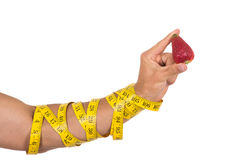 Man's arm wrapped in measuring tape holding red Royalty Free Stock Photos