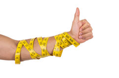 Man's arm wrapped in measuring tape holding thumb Stock Photography