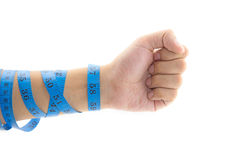 Man's arm wrapped in measuring tape holding thumb up Royalty Free Stock Photography