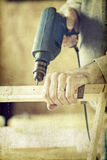 Man's arms drill lath in the workshop Stock Photography