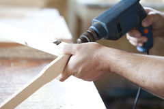 Man's arms drill lath in the workshop Stock Photos