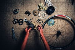 The man`s arms are repairing the bicycle. everywhere there are spare parts without any logos. The man`s arms are repairing the bicycle. everywhere there are royalty free stock images