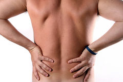 Man's back. A young man is holding his back in pain Royalty Free Stock Photos