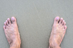 Man's Bare Feet on the beach. Sand texture. royalty free stock image