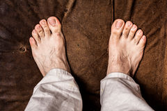 Man's bare feet on brown texture Royalty Free Stock Image