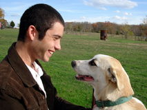 Man's Best Friend. A young man playing with his hound dog Stock Photography