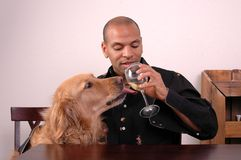 Man's Best Friend. A man shares some champagne with his dog Royalty Free Stock Image
