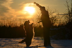 Man's best friend. Man and his best friend dancing in the snow Royalty Free Stock Photo