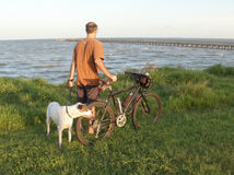 Man's best friend and mountain bike. Male cyclist with his dog walking with his bike along shoreline Royalty Free Stock Images