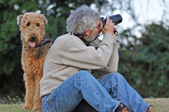 Man's best friend. Photographer and Airedale dog. Photographer man taking photos with his pet Airedale dog by his side stock photography