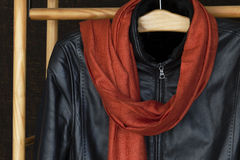 A man's black leather jacket and a scarf. Hanging in a wardrobe Royalty Free Stock Photo