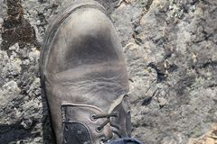 Man`s construction boot resting on a rocky surface. stock photos