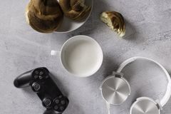 Man`s breakfast with game. Earphones,coffee, cinnamon bun stock image