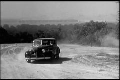 Man in 1940s car driving up to farmhouse