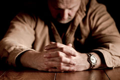 Man's Clasped Hands. Dark, emotional image of clasped hands on troubled man Stock Photography