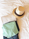 Man's cloth and towel on messy bed prepare for summer travel Stock Image