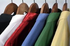 Man's clothing. Choice of stylish colorful shirts on wooden hangers royalty free stock image
