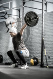 Man's crossfit workout with barbell. Wonderful man with a beard raises a barbell above his head in the squat in the gym on the gray brick wall background. He Stock Photos