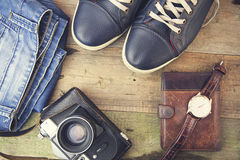 Man`s different accessories. Keds, jinse, watch, wallet and camera on wooden background Stock Photos