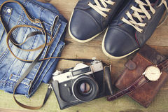 Man`s different accessories. Keds, jinse, watch, wallet and camera on wooden background Royalty Free Stock Images