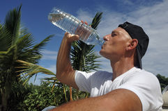 Man's drinking. A bottle of water Royalty Free Stock Image