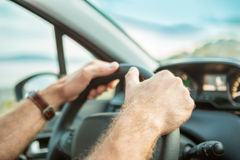 Man's (driver's) hands on steering wheel inside a car. Man's (driver's) hands on steering wheel while driving a car - close up Royalty Free Stock Image