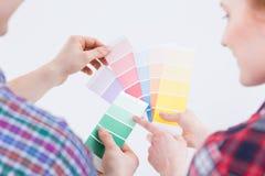 Man ` s en vrouwen` s handen die kleurenplukkers nemen stock foto's