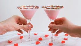 Man ` s en vrouwen` s handen die roze melkcocktail, close-up nemen Verfraaid met geleiharten De Dag van heilige Valentine ` s stock footage