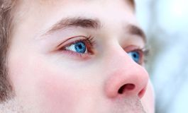 Man's face in close-up. Man face close-up. Beautiful blue eyes looking into the distance Royalty Free Stock Photography