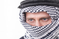 Man's face covered with Arab scarf Stock Photos