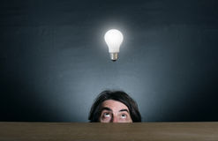 Man's face looking at the  light bulb. Royalty Free Stock Photo