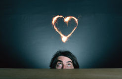 Man's face looking  at the sparkling heart Royalty Free Stock Images