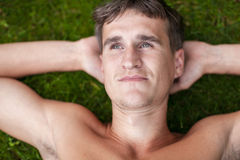Man's face, lying on the grass Royalty Free Stock Image