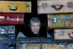 Man's Face Surrounded by Suitcases Royalty Free Stock Image