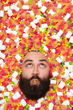 Man`s face surrounded with sweet stuff. Bearded man holding candy in mouth surrounded fruit jellies and marshmallows Stock Photography