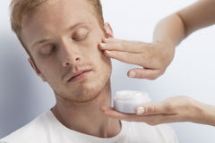 Man's facial cosmetic treatment. royalty free stock photography