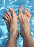 Man's feet on the bathtub of a relaxing pool Royalty Free Stock Image