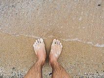 Man 's feet on the beach. Stock Photography