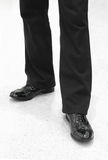 Man's feet in black trousers and leather shoes Royalty Free Stock Images