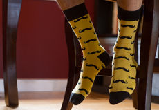Man's feet with fancy socks printed with moustaches. Yellow and black moustache printed socks on man's feet rested against chair. Gift. Ideal for e-commerce royalty free stock photos
