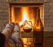 Man`s Feet before fireplace, red wine in a glass. Man`s Feet in socks; before; fireplace; red wine in a glass and bottle, in country house, winter vacation royalty free stock images