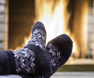Man`s Feet in gray socks, before  fireplace, in country house. Royalty Free Stock Photos